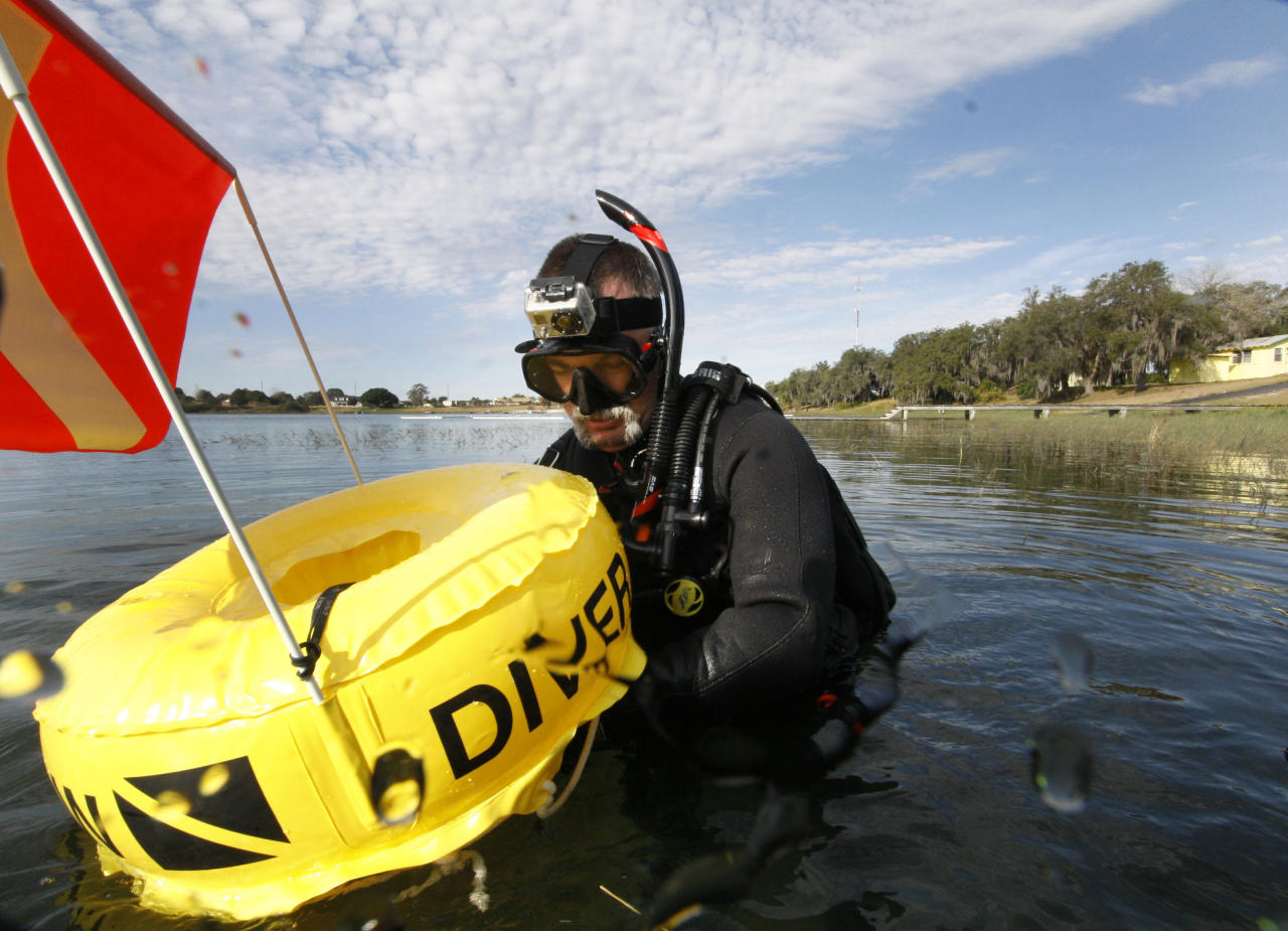 "In this Saturday, Jan. 14, 2012 photo, Kenny Jenkins hooks a line to a float with a ""Diver Down"" flag as he prepares to place a geocache in about 33 ft. of water in Lake Denton in Avon Park Fla. Interest in geocaching has grown significantly over the years. But combining the two hobbies, geocaching and scuba diving, has only recently taken off. About 100 geocaches around the world today are only accessible with scuba gear, according to the geocaching.com database. (AP Photo/Wilfredo Lee)"