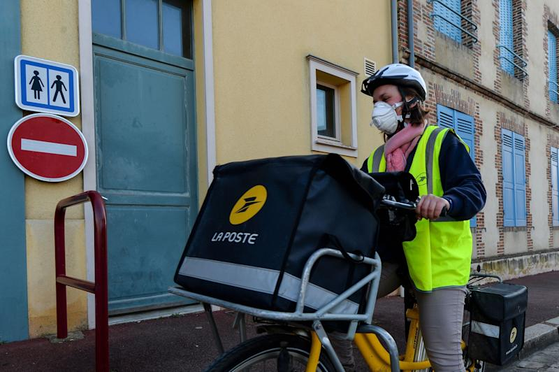 Postal workers have continued to deliver mail and packages throughout the pandemic. (Photo: JEAN-FRANCOIS MONIER/AFP via Getty Images)