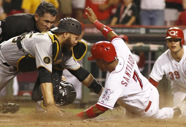 Cincinnati Reds' Ramon Santiago (7) is tagged out by Pittsburgh Pirates catcher Russell Martin, left, in the 10th inning of a baseball game, Saturday, July 12, 2014, in Cincinnati. The Pirates won 6-5 in 11 innings. (AP Photo/David Kohl)