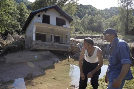 Two men stand near a house tilted by floods in the town of Valjevo, southwest from Belgrade May 21, 2014. Picture taken May 21. REUTERS/Marko Djurica