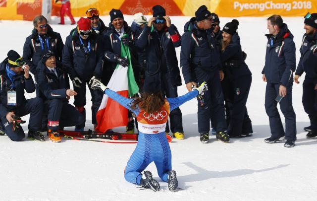 Alpine Skiing - Pyeongchang 2018 Winter Olympics - Women's Downhill - Jeongseon Alpine Centre - Pyeongchang, South Korea - February 21, 2018 - Gold medallist Sofia Goggia of Italy kneels in front of her coaches and team members. REUTERS/Leonhard Foeger
