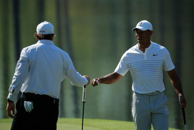 U.S. golfers Tiger Woods (R) and Phil Mickelson talk on the 16th green during the second day of practice for the 2018 Masters golf tournament at Augusta National Golf Club in Augusta, Georgia, U.S. April 3, 2018. REUTERS/Brian Snyder