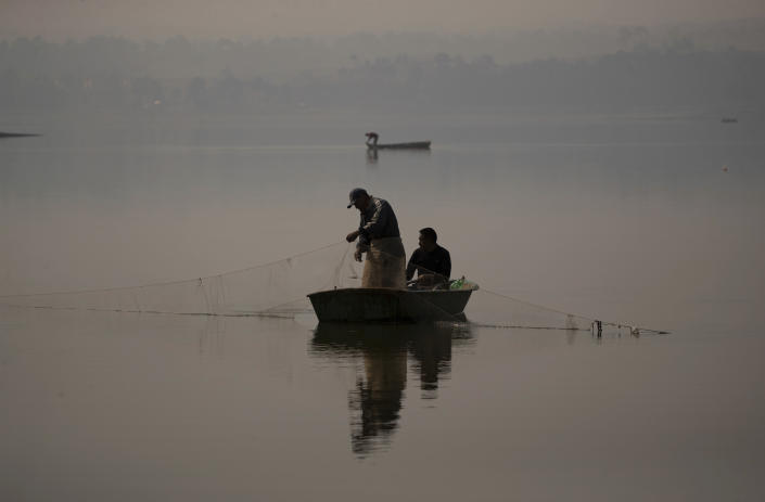 Fishermen fish in the waters of the Villa Victoria Dam, the main water supply for Mexico City residents, on the outskirts of Toluca, Mexico Thursday, April 22, 2021. Drought conditions now cover 85% of Mexico, and in areas around Mexico City and Michoacán, the problem has gotten so bad that lakes and reservoirs are drying up. (AP Photo/Fernando Llano)
