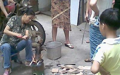 The woman could be seen roasting the puppy with people watching on including children. (Screengrab from ww.chinasmack.com)