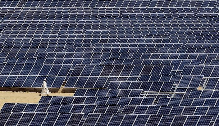 An Indian worker walks past lines of solar panels at Roha Dyechem solar plant in the western Indian state of Rajasthan on August 23, 2015 (AFP Photo/Money Sharma)