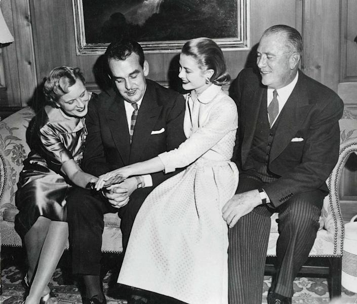 """<p>Prince Rainier and Kelly staged a photo-op in her family home in Philadelphia, alongside her parents, in January 1956. The actress shows off her engagement ring, a 10.48-carat <a href=""""https://www.townandcountrymag.com/style/jewelry-and-watches/a27698288/charlotte-casiraghi-princess-grace-wedding-jewelry/"""" rel=""""nofollow noopener"""" target=""""_blank"""" data-ylk=""""slk:emerald-cut diamond"""" class=""""link rapid-noclick-resp"""">emerald-cut diamond</a> from Cartier. </p>"""