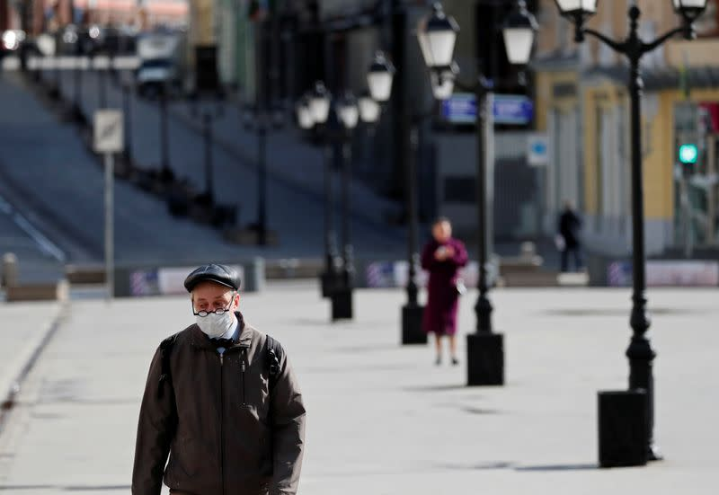 A man wearing a protective face mask walks along the street in Moscow