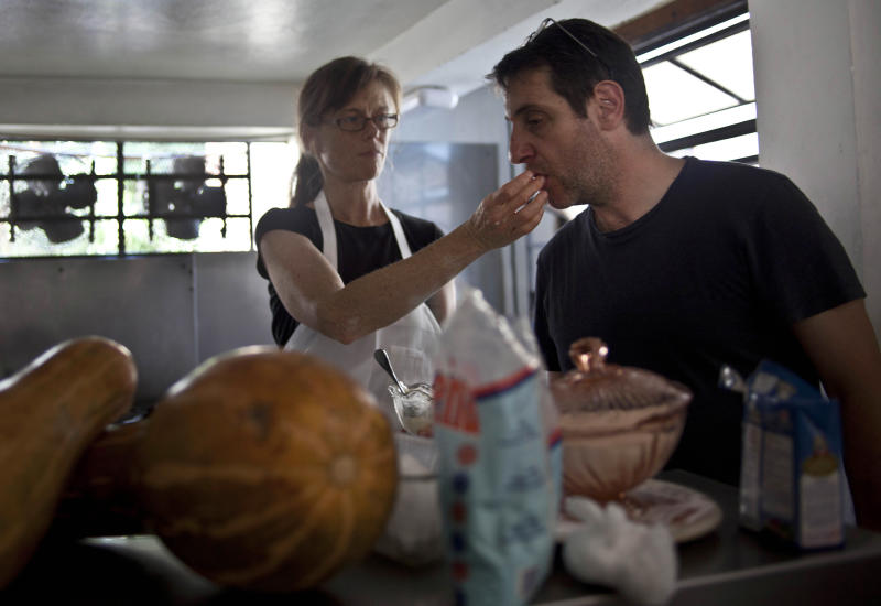 "In this Dec. 7, 2012 photo, U.S. chef Kelsie Kerr gives a taste to fellow chef Jerome Waag as she prepares dinner at the private restaurant Le Chansonnier in Havana, Cuba. Kerr and Waag visited Cuba as part of the ""Planting Seeds"" delegation that held give-and-take seminars with chefs and culinary students about slow food. They also put on two massive dinners including a rabbit-based meal at the privately run Le Chansonnier. Their advice to Cuban cooks who struggle with unreliable supply of even basic ingredients like eggs: Be flexible, and don't worry too much about maintaining a fixed menu. (AP Photo/Ramon Espinosa)"