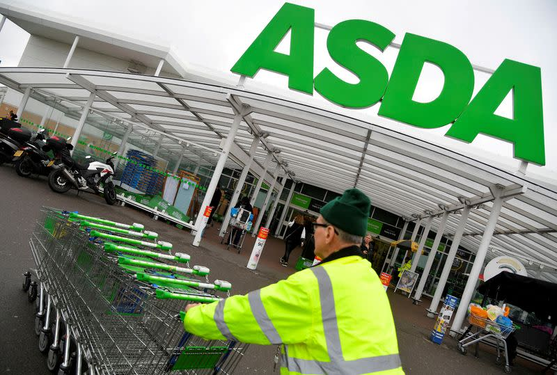FILE PHOTO: FILE PHOTO: A worker pushes shopping trolleys at an Asda store in West London, Britain