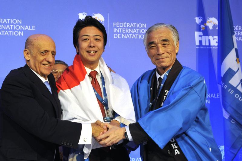 FILE - In this Jan. 31, 2016 file photo, from left, President of International Swimming Federation, FINA, Julio Maglione, President of the Japanese Swimming Federation Tsuyoshi Aoki and Mayor of Fukuoka, Japan, Soichiro Takashima shake hands after Fukuoka was announced to host the 2021 FINA world aquatics championships during a meeting of FINA leaders in Budapest, Hungary. On Monday, March 30, 2020, the Tokyo Games were pushed back a full year by the coronavirus pandemic, to the same period of the biannual aquatics, causing the swimming's governing body to go back to the drawing board to figure out when to hold its next world championships. (Attila Kovacs/MTI via AP, file)