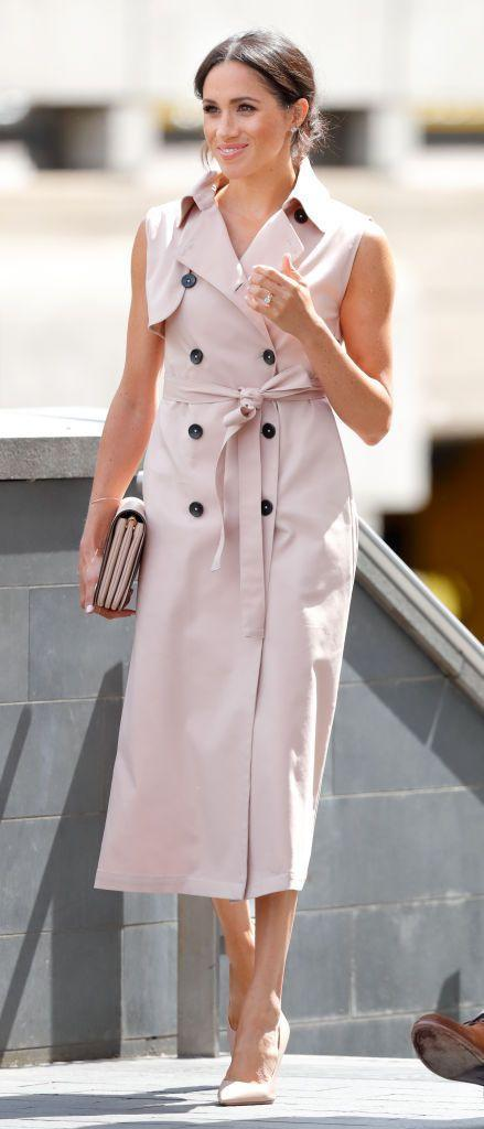 """<p>For a visit to the <span class=""""redactor-unlink"""">Nelson Mandela Centenary Exhibition</span> in London, Meghan opted for a blush pink sleeveless trench by Canadian brand House of Nonie paired with matching stilettos and <span class=""""redactor-unlink"""">Mulberry England Clifton Shoulder Bag</span> in blush calfskin, July 2018. </p>"""