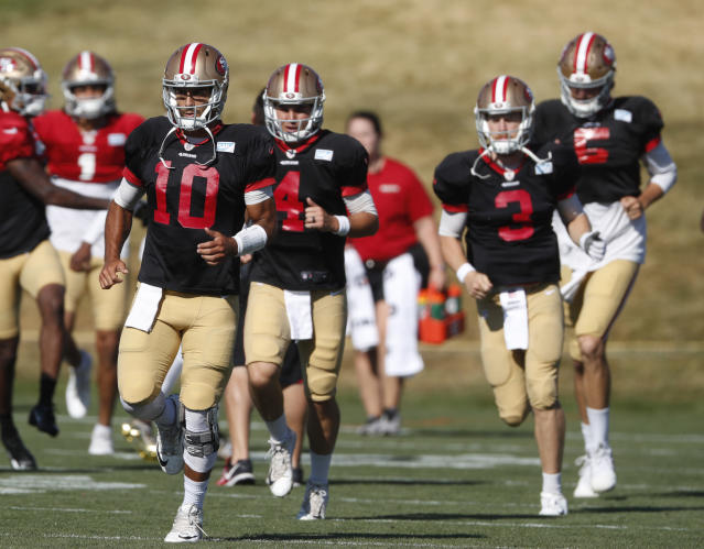 San Francisco 49ers quarterback Jimmy Garoppolo leads quarterbacks through a drill during a combined NFL training camp with the Denver Broncos Saturday, Aug. 17, 2019, at the Broncos' headquarters in Englewood, Colo. (AP Photo/David Zalubowski)