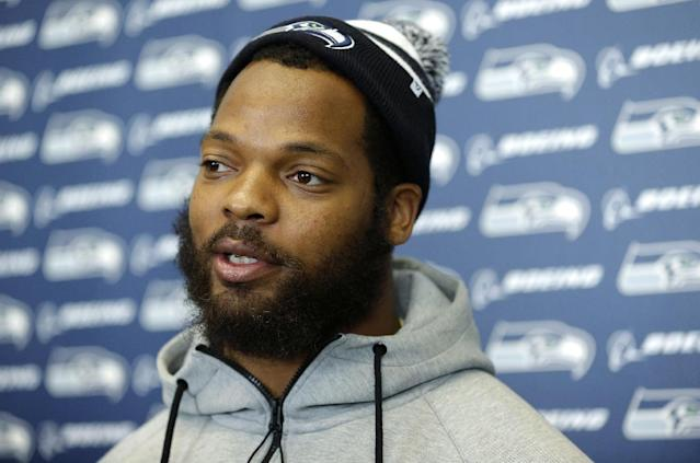Seattle Seahawks defensive end Michael Bennett talks to reporters, Monday, March 10, 2014, at the team's headquarters in Renton, Wash. The Seahawks announced Monday that Bennett, who was one of the top NFL football free agents this year, had signed a multi-year deal with the Super Bowl champion Seahawks. (AP Photo/Ted S. Warren)