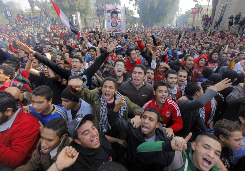 """Egyptian soccer fans of Al-Ahly club celebrate in front of their club in Cairo, Egypt, Saturday, Jan. 26, 2013. An Egyptian court sentenced 21 people to death on charges related to one of the world's deadliest incidents of soccer violence, which killed 74 mostly teenage fans of Egypt's most popular sports club last year. Poster in background showing one of the victims with Arabic reads """"martyr Hamed Fathi Hamed."""" (AP Photo/Amr Nabil)"""