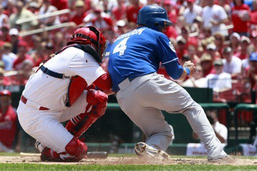 St. Louis Cardinals catcher Yadier Molina, left, tags out Kansas City Royals' Alex Gordon (4) at home during the first inning of a baseball game Saturday, June 16, 2012, in St. Louis. (AP Photo/Jeff Roberson)