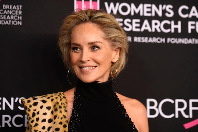Sharon Stone looks breath-taking in this turtle neck dress with a leopard skin scarf on her shoulder
