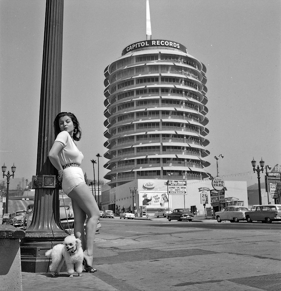 """<p>Who wears short shorts? Joan Bradshaw! Posing in front of Capitol Records with a cute pup, she starred in a few films but is most well-known for her producing career. </p><p><strong>RELATED:</strong> <a href=""""https://www.goodhousekeeping.com/life/entertainment/g3775/it-girls-through-the-years/"""" rel=""""nofollow noopener"""" target=""""_blank"""" data-ylk=""""slk:Find Out Who the Hollywood &quot;It Girl&quot; Was the Year You Were Born"""" class=""""link rapid-noclick-resp"""">Find Out Who the Hollywood """"It Girl"""" Was the Year You Were Born</a></p>"""