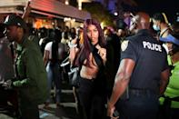A police officer informs people of an 8 pm curfew on March 21, 2021 in Miami Beach, Florida