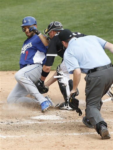 Los Angeles Dodgers' James Loney, left, is tagged out by Chicago White Sox catcher A.J. Pierzynski, center, as home plate umpire Dan Bellino, right, leans in for a closer look in the fifth inning of a spring training baseball game Monday, March 5, 2012, in Glendale, Ariz. (AP Photo/Paul Connors)