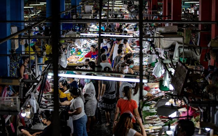 Filipinos flock a wet market to stock up on food a day before a strict lockdown is reimposed in Manila and nearby provinces on March 28, 2021 in Quezon city, Metro Manila, Philippines - Ezra Acayan