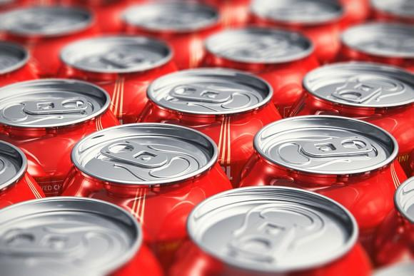 Pop cans lined up on a table.