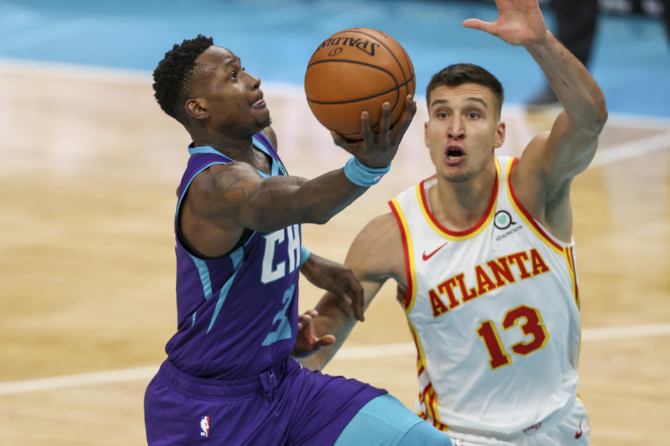 Charlotte Hornets guard Terry Rozier, left, drives to the basket against Atlanta Hawks guard Bogdan Bogdanovic, right, during the third quarter of an NBA basketball game in Charlotte, N.C., Sunday, April 11, 2021. (AP Photo/Nell Redmond)