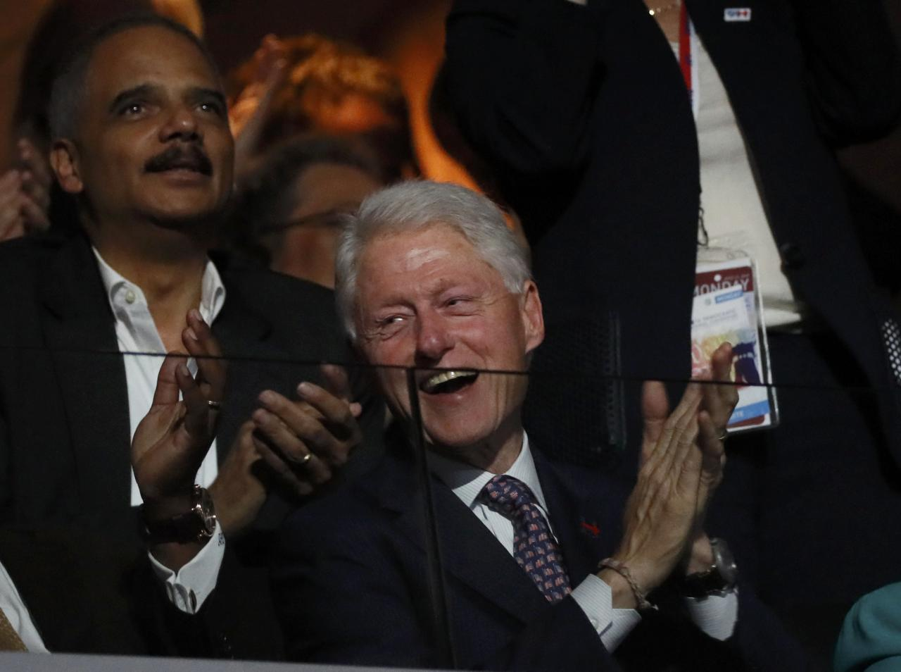 Former U.S. President Bill Clinton reacts to the speech by first lady Michelle Obama as former Attorney General Eric Holder (rear) applauds at the Democratic National Convention in Philadelphia, Pennsylvania, U.S. July 25, 2016.  REUTERS/Mike Segar