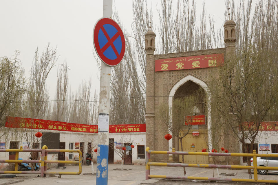 """A mosque with the banner """"Love the Party, Love the Country"""" is seen near Shule county in northwestern China's Xinjiang Uyghur Autonomous Region on March 20, 2021. Four years after Beijing's brutal crackdown on largely Muslim minorities native to Xinjiang, Chinese authorities are dialing back the region's high-tech police state and stepping up tourism. But even as a sense of normality returns, fear remains, hidden but pervasive. (AP Photo/Ng Han Guan)"""
