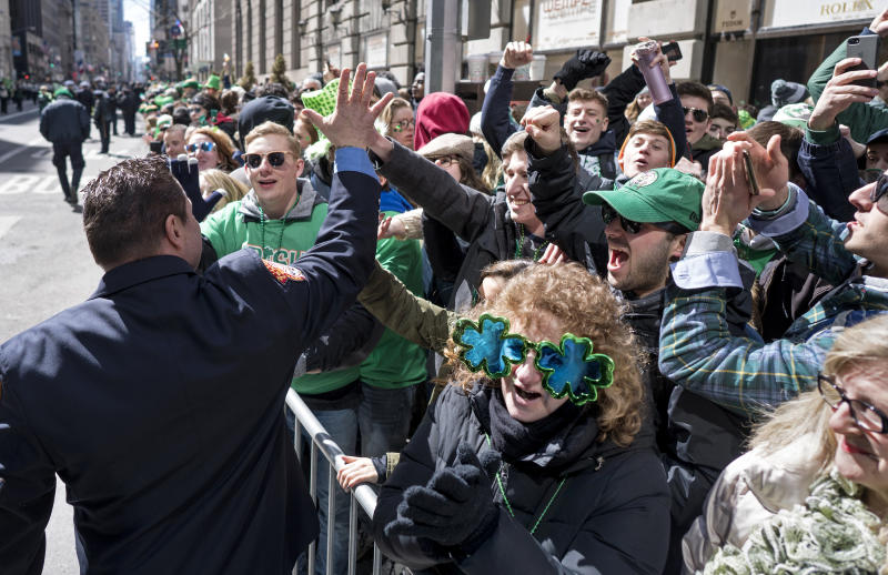 "A New York City firefighter high fives spectators as they take part in the St. Patrick's Day parade Saturday, March 17, 2018, in New York. Several bagpipe bands led a parade made up of over 100 marching bands after Democratic Gov. Andrew Cuomo spoke briefly, calling it a ""day of inclusion"" and adding: ""We're all immigrants."" (AP Photo/Craig Ruttle)"