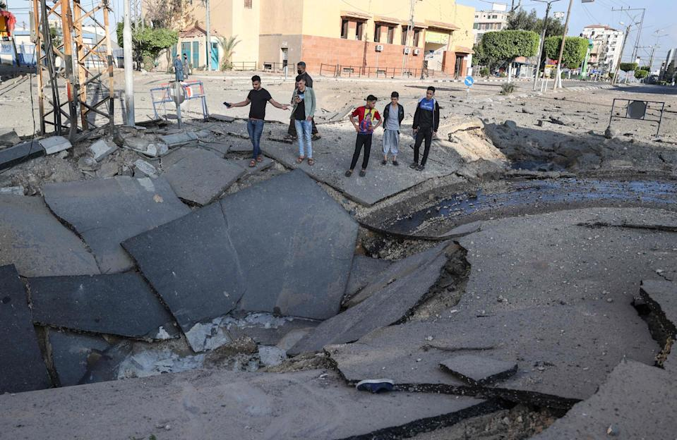 Palestinian youths take pictures with their smart phones of a huge crater on a main road in Gaza CityAFP via Getty Images
