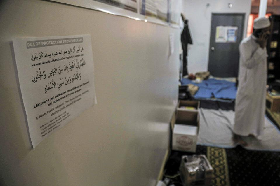 """In this Wednesday, April 22, 2020, photo, a prayer of """"protection from diseases"""" is printed in Arabic and English on a paper posted to the wall of the An-Noor Cultural Center and masjid, which serves a mostly Bangladeshi Muslim community in the Elmhurst neighborhood in the Queens borough of New York. """"Close to 150 people we lost in this COVID19 crisis,"""" said Ismail, citing the death toll from the coronavirus outbreak on the Bangladeshi community, some who frequented the center only a few blocks from Elmhurst Hospital—the city's deadliest hospital for stricken patients. (AP Photo/Bebeto Matthews)"""