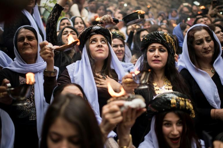 Iraqi Yazidis light candles and paraffin torches outside Lalish temple, the holiest shrine of their faith, during a ceremony on April 18, 2017 to mark the eve of Yazidi New Year