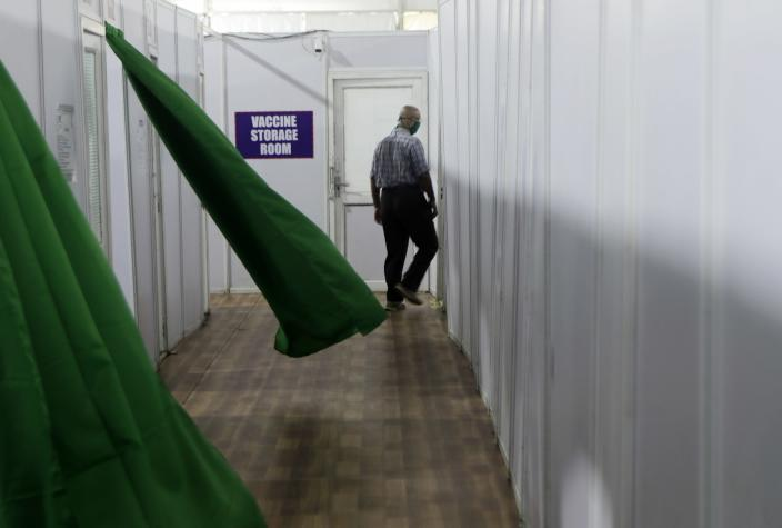 """FILE - In this Friday, Jan. 8, 2021, file photo, a health worker walks past a storage room during a trial run of COVID-19 vaccine delivery system, as India's prepare to kick off the coronavirus vaccination drive on Jan. 16, in Mumbai, India. There has been growing apprehensions among health care workers after India took a regulatory shortcut to approve a vaccine by the Bharat Biotech before late clinical trials showed it was effective in preventing illness from coronavirus infections. The Indian drugmaker's chairman and managing director Krishna Ella has since admitted that the vaccine's effectiveness against the U.K. variant was """"only a hypothesis."""" (AP Photo/Rajanish Kakade, File)"""