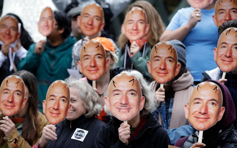 "In this Oct. 31, 2018, file photo, demonstrators hold images of Amazon CEO Jeff Bezos near their faces during a Halloween-themed protest at Amazon headquarters over the company's facial recognition system, ""Rekognition,"" in Seattle. San Francisco is on track to become the first U.S. city to ban the use of facial recognition by police and other city agencies as the technology creeps increasingly into daily life. Studies have shown error rates in facial-analysis systems built by Amazon, IBM and Microsoft were far higher for darker-skinned women than lighter-skinned men. - Elaine Thompson/AP"