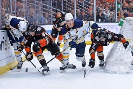Oct 15, 2017; Anaheim, CA, USA; Anaheim Ducks right wing Jakob Silfverberg (33) and left wing Andrew Cogliano (7) battle for the puck with Buffalo Sabres defenseman Nathan Beaulieu (82) and center Jack Eichel (15) during the third period at Honda Center. Mandatory Credit: Jake Roth-USA TODAY Sports