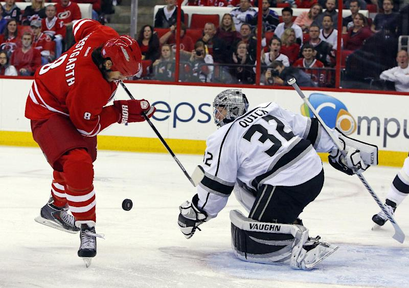 Carolina Hurricanes' Kevin Westgarth (8) tries to gather the puck in front of Los Angeles Kings goaltender Jonathan Quick (32) during the second period of an NHL hockey game, Friday, Oct. 11, 2013, in Raleigh, N.C. (AP Photo/Karl B DeBlaker)