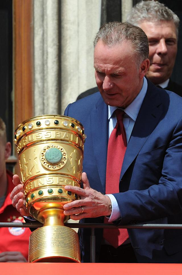 Bayern Munich's CEO Karl-Heinz Rummenigge holds the DFB German Cup trophy on the balcony of Munich's town hall, on May 18, 2014 (AFP Photo/Angelika Warmuth)
