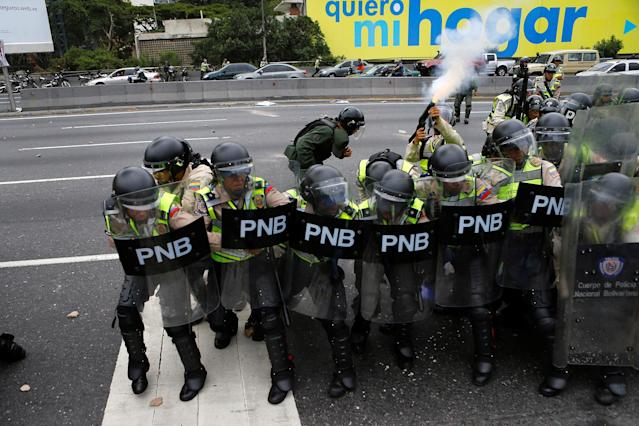 <p>A riot policeman shoots tear gas during a clash with opposition supporters at a rally to demand a referendum to remove President Nicolas Maduro in Caracas, June 7, 2016. (Reuters/Ivan Alvarado) </p>