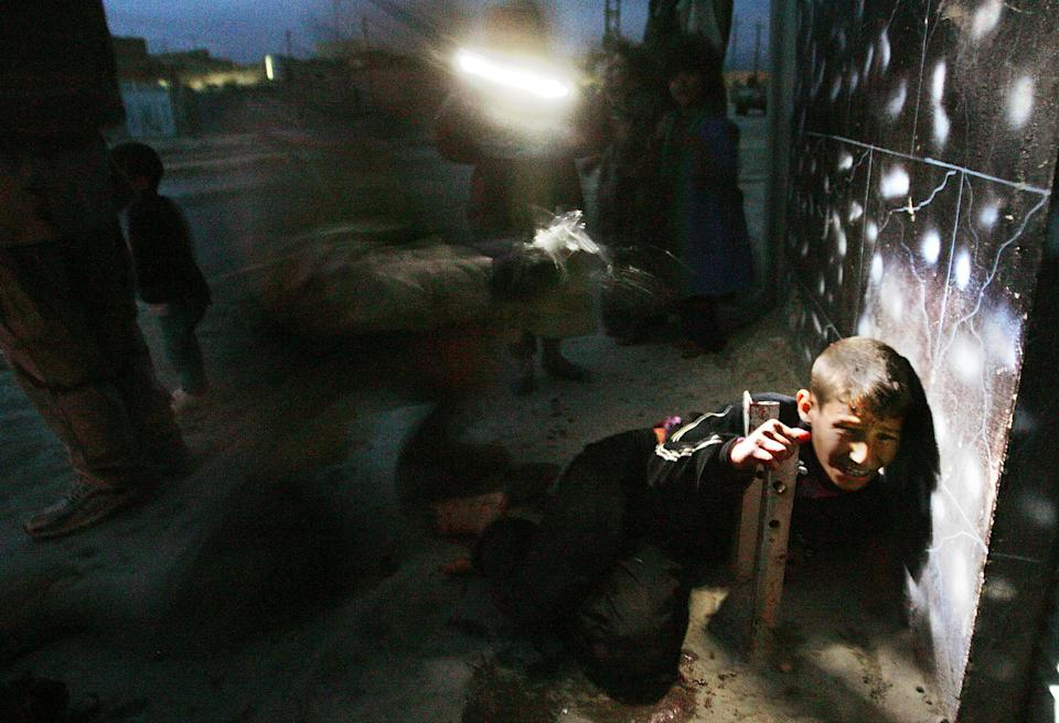 <p>Rakan Hassan, then 11, is treated by a medic seconds after being accidentally shot by U.S. soldiers January 18, 2005 in Tal Afar, Iraq. Racan's parents were shot and killed and he was gravely wounded in the incident in the restive northern Iraqi city. The incident was widely publicized, and ultimately led to Racan's treatment in Boston. With nerve damage to his abdomen and spine, doctors thought Racan might never walk again, but an intensive physical therapy regimen has brought back the use of his legs and he can now walk with assistance. Racan was returned to Iraq with his siblings. (Photo by Chris Hondros/Getty Images) </p>