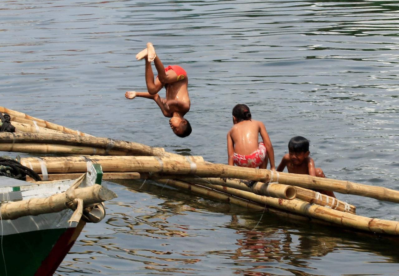 A boy jumps into the polluted water of Manila Bay ahead of World Water Day in Tondo city, Metro Manila, Philippines March 21, 2018. REUTERS/Romeo Ranoco