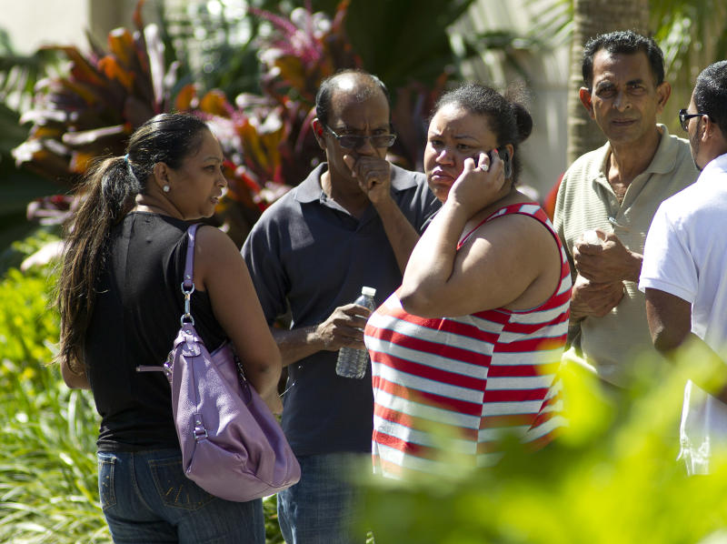 Unidentified family members of Robert Budhoo, who is missing after a parking garage collapsed at the Miami Dade College West campus in Doral, Fla., wait for results of the search through the rubble Thursday, Oct. 11, 2012, in Doral. (AP Photo/J Pat Carter)