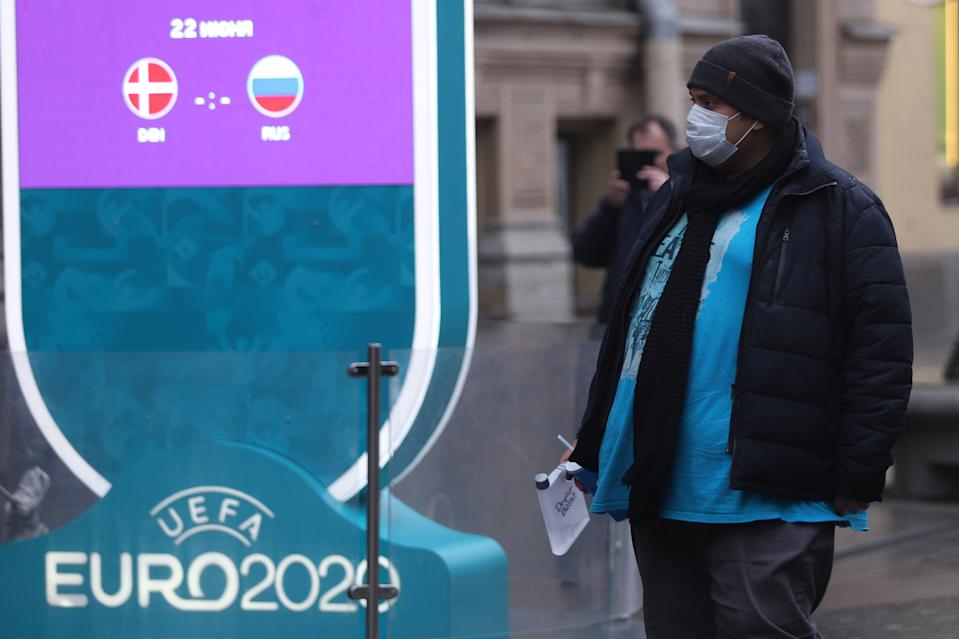 A man wearing a mask as a protective measure, walks past a logo of UEFA Euro 2020 at a countdown clock showing 450 days to the tournament.
