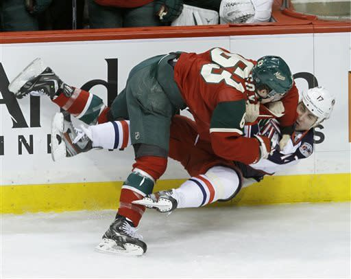 Minnesota Wild right wing Charlie Coyle (63) and Columbus Blue Jackets center Brandon Dubinsky (17) fall to the ice as they fight during the first period of an NHL hockey game in St. Paul, Minn., Saturday, April 13, 2013. (AP Photo/Ann Heisenfelt)