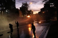 Anti-government protesters face off with a police water cannon in Santiago, Chile, Friday, Nov. 1, 2019. Chile has been facing days of unrest, triggered by a relatively minor increase in subway fares. The protests have shaken a nation noted for economic stability over the past decades, which has seen steadily declining poverty despite persistent high rates of inequality. (AP Photo/Rodrigo Abd)