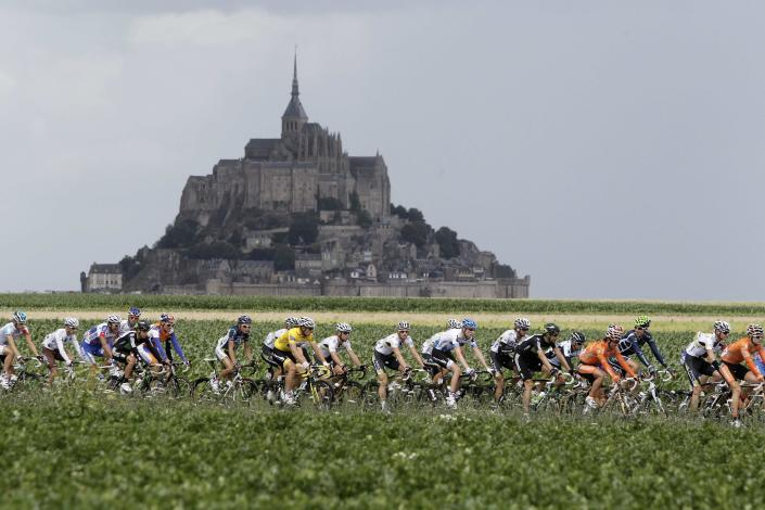 The pack passes world heritage site Mont Saint Michel, rear, a rocky tidal island which holds a monastery, during he sixth stage of the Tour de France cycling race over 226.5 kilometers (140.7 miles) starting in Dinan, Brittany, and finishing in Lisieux, Normandy, western France, Thursday July 7, 2011. (AP Photo/Laurent Cipriani)