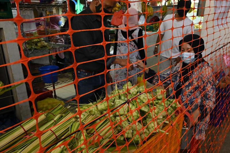 People wearing face masks amid concern over the spread of the COVID-19 coronavirus buy traditional delicacies, a custom ahead of Eid al-Fitr which marks the end of the Muslim holy month of Ramadan, at the Geylang Serai market installed with crowd control screen in Singapore on May 21, 2020. (Photo by Roslan RAHMAN / AFP) (Photo by ROSLAN RAHMAN/AFP via Getty Images)