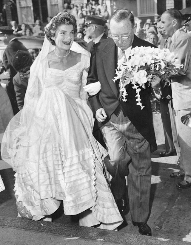 A smiling Jacqueline Bouvier arrives at St. Mary's Church in Newport, R.I., on the arm of her stepfather, Hugh D. Auchincloss, for her wedding. (Photo by Pat Candido/NY Daily News Archive via Getty Images)