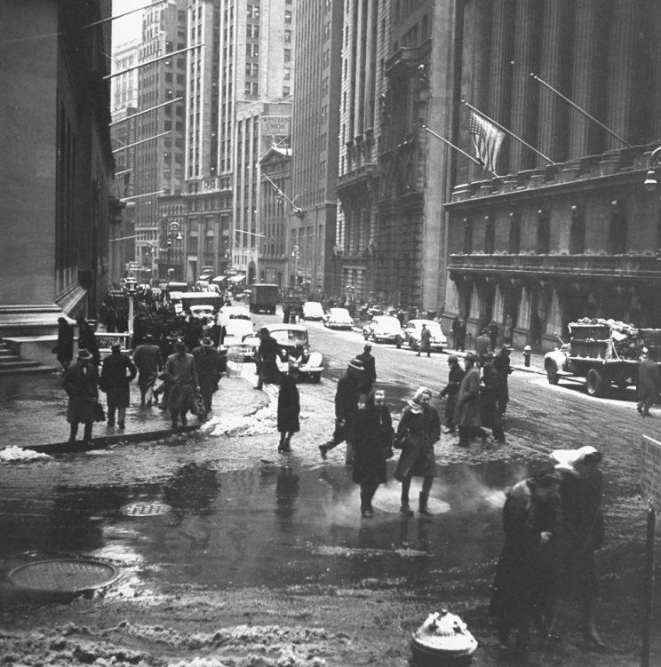 Old photo of New Yorkers walking through slush-covered streets.