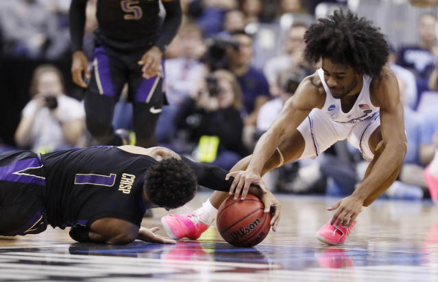 Washington's David Crisp (1) and North Carolina's Coby White (2) battle for a loose ball in the first half during a second round men's college basketball game in the NCAA Tournament in Columbus, Ohio, Sunday, March 24, 2019. (AP Photo/John Minchillo)