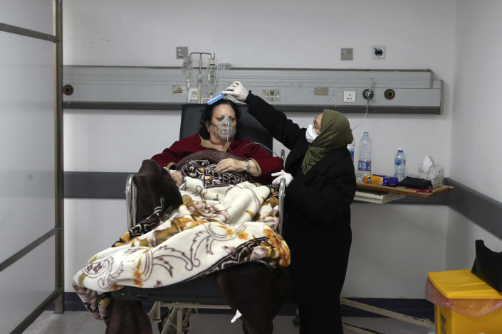 A woman combs the hair of her sister, a COVID-19 patient, at the intensive care unit of the Rafik Hariri University Hospital in Beirut, Lebanon, Friday, Jan. 22, 2021. Hospitals in Lebanon are reaching full capacity amid a dramatic surge in coronavirus cases across the crisis-hit Mediterranean nation even amid strict lockdown. (AP Photo/Bilal Hussein)